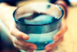 woman holding a large glass of water